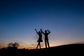 Lovers admire the beautiful sky and waving their hands relax in nature camping a couple enjoying sunset Royalty Free Stock Images