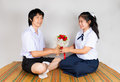 Lovers of asian thai high school students boyfriend gives flower to girlfriend Stock Image