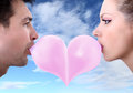 Lovers couple kiss heart shaped valentine day with chewing gum on sky background Royalty Free Stock Photos