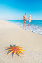 Lovers couple at sandy sea beach with red starfish big hot countries holidays concept Royalty Free Stock Images