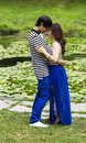 Lovers holding each other closely vertical photo of young adult couple very with the lily pond in background Royalty Free Stock Photos
