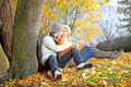 Lovers man and woman setting in autumn forest men women under the tree Stock Photography