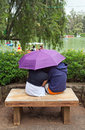 Lovers in the park baguio city philippines july two young sit huddled cuddling under an umbrella burnham on july baguio city Royalty Free Stock Images
