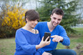 Lovers in the park looking the mobile phone Royalty Free Stock Photo
