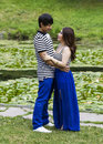 Lovers at the pond vertical photo of young adult couple looking each other with in background Stock Images
