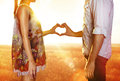 Lovers in sun beams silhouette of hands form of heart when sweethearts have touched Royalty Free Stock Photography
