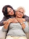 Loving adult daughter embracing old mother attractive brunette middle age women her senior isolated on white background is sitting Stock Photos