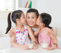 Loving asian family happy mother and daughters drinking milk at home children kissing mother parent and children beautiful model Royalty Free Stock Images