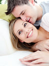 Loving boyfriend hugging his girlfriend on a sofa Stock Images