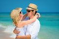 Loving couple on a clean blue sea happy embracing young in sunglasses hats and white dress tropical beach with background Royalty Free Stock Photos