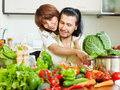 Loving couple cooking veggy lunch in home kitchen Stock Photo