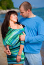 Loving couple embracing on coast of blue sea Stock Photos