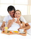 Loving couple having breakfast lying in the bed Stock Images