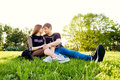 A loving couple hugging sitting on the grass in the park Royalty Free Stock Photo