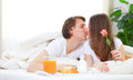 Loving couple kissing and having breakfast in bed Royalty Free Stock Photo