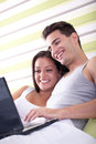 Loving couple with laptop and lying in bed Stock Photo