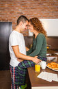 Loving couple looking at each other in a home portrait of young while having breakfast on the kitchen Stock Image