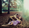 A loving couple lying on autumn leaves Stock Images