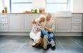 Loving couple sitting on kitchen floor