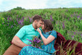 Loving couple sitting together in the middle of flowers on a meadow. Honeymoon Royalty Free Stock Photo