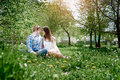 Loving couple in the spring garden sitting on the grass Royalty Free Stock Photo