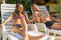 Loving couple sunbathe on the sun loungers on the beach Royalty Free Stock Photos