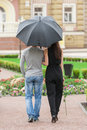 Loving couple with umbrella rear view of young walking on street while men holding Stock Photos