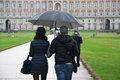 Loving couple with umbrella rear view of young walking on street while men holding Royalty Free Stock Photos