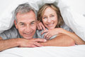 Loving couple under the duvet smiling at camera in bedroom at home Stock Photos
