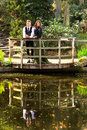 Loving couple in victorian fashion near lake with reflections in park men and women or edwardian vintage clothing the the water on Stock Image
