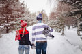 Loving couple walking on a date in a winter Park. On the back of a guy hangs a pair of skates Royalty Free Stock Photo