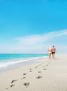 Loving couple walking with footprints at sea Royalty Free Stock Photo