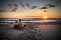 Loving couple watching sunset and their dog beautiful near the sea Stock Photography