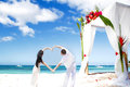 Loving couple on wedding day tropical beach near bamboo arch with flowers Royalty Free Stock Images