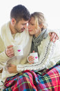 Loving couple in winter clothing with coffee cups young against bright background Stock Photo