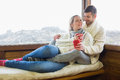Loving couple in winter wear with cups against cabin window young clothing coffee sitting Royalty Free Stock Photos