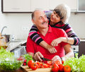 Loving elderly couple cooking together in home kitchen Royalty Free Stock Images
