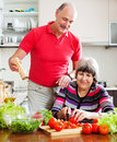 Loving elderly couple cooking with tomatoes in home kitchen Royalty Free Stock Image