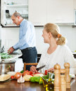 Loving elderly couple doing housework and cooking together in domestic kitchen Royalty Free Stock Photography
