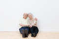 Loving elderly couple in their new home sitting side by side on the bare wooden floor smiling satisfaction Stock Images
