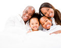 Loving family in bed lying and smiling isolated over white Royalty Free Stock Images