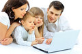 Loving family looking at a laptop lying down on bed home Royalty Free Stock Photos