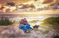 Loving family at sunset sea couple and their dog watching beautiful near the Stock Image