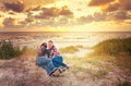 Loving family at sunset sea couple and their dog watching beautiful near the Stock Photography