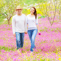 Loving family walk in park handsome guy wearing hat and cute girl holding pink flowers bouquet walking spring romantic feelings Stock Images