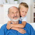 Loving grandfather and grandson with his eyes closed in love appreciation as his adorable young hugs him from behind with his arms Royalty Free Stock Photo