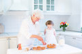 Loving grandmother baking apple pie with toddler girl an her adorable granddaughter Royalty Free Stock Images