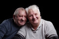 A loving handsome senior couple on a black background Stock Image