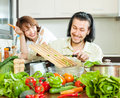 Loving happy couple cooking veggy lunch in kitchen Royalty Free Stock Image