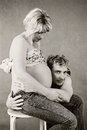 Loving happy couple pregnant woman with her husband a young father laying his head on the swollen belly of his wife listening to Royalty Free Stock Images